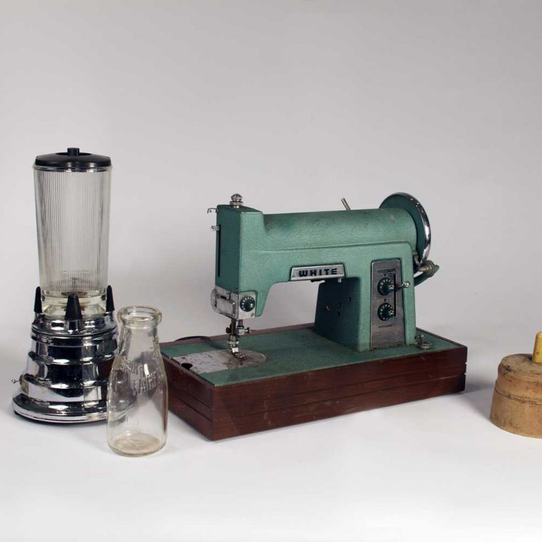 Waring Blender, 1947; Milk bottle, mid-20th century; Sewing Machine, late 19th century; Butter mold, 1920s. Photo by Museum staff.