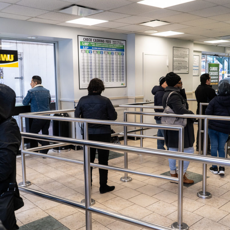 March 22, 2020: Inside a busy PLS Check Cashing store on Roosevelt Avenue at Junction Boulevard, Queens, New York. © Camilo José Vergara