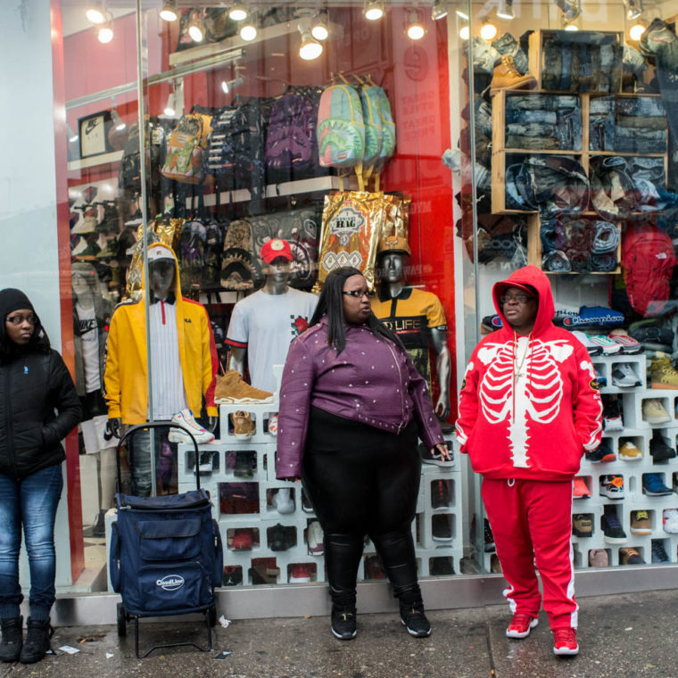 March 30, 2020: One person stands wearing drab winter clothes in contrast with the studied flamboyance of the other two. One wearing a jogging outfit with a rib cage design. Notice the use of cinderblocks for displaying sneakers. Dr. Jay's, 410 Westchester Avenue, Bronx, New York. © Camilo José Vergara