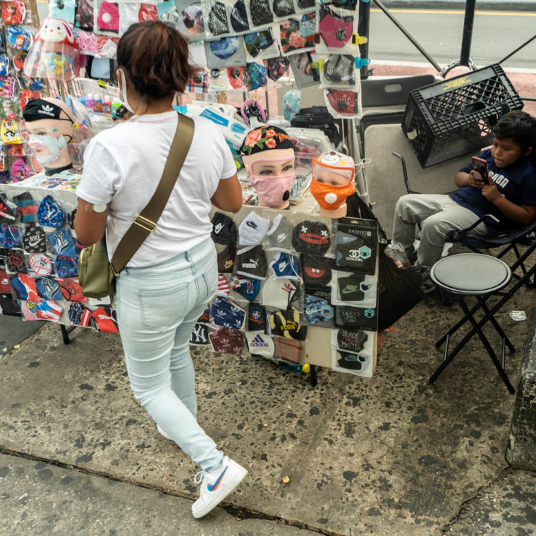 September 17, 2020: Selling masks while taking care of her child. East 149th Street at Melrose Avenue, Bronx, New York. © Camilo José Vergara
