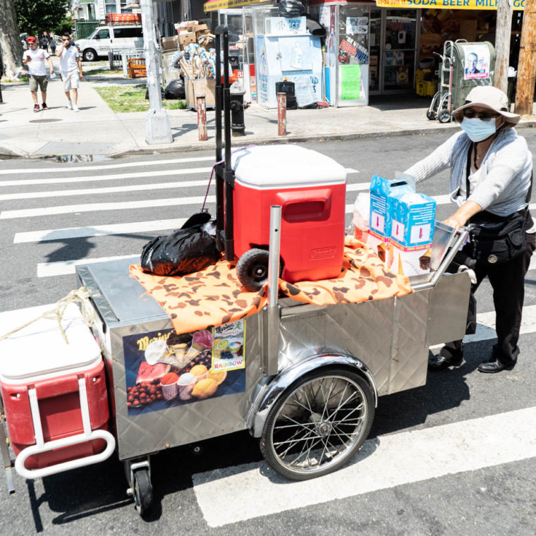 July 25, 2020: Maria, originally from Ecuador, on her way to her spot to sell Italian ices. 37th Avenue at 99th Street, Queens, New York. © Camilo José Vergara
