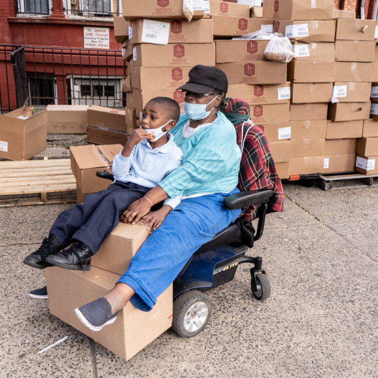 September 11, 2020: Barbara and her great-grandchild carrying two boxes of bread on her motorized wheelchair. Saint James Social Services Corporation, 604 Dr. Martin Luther King Jr. Boulevard, Newark, New Jersey. © Camilo José Vergara