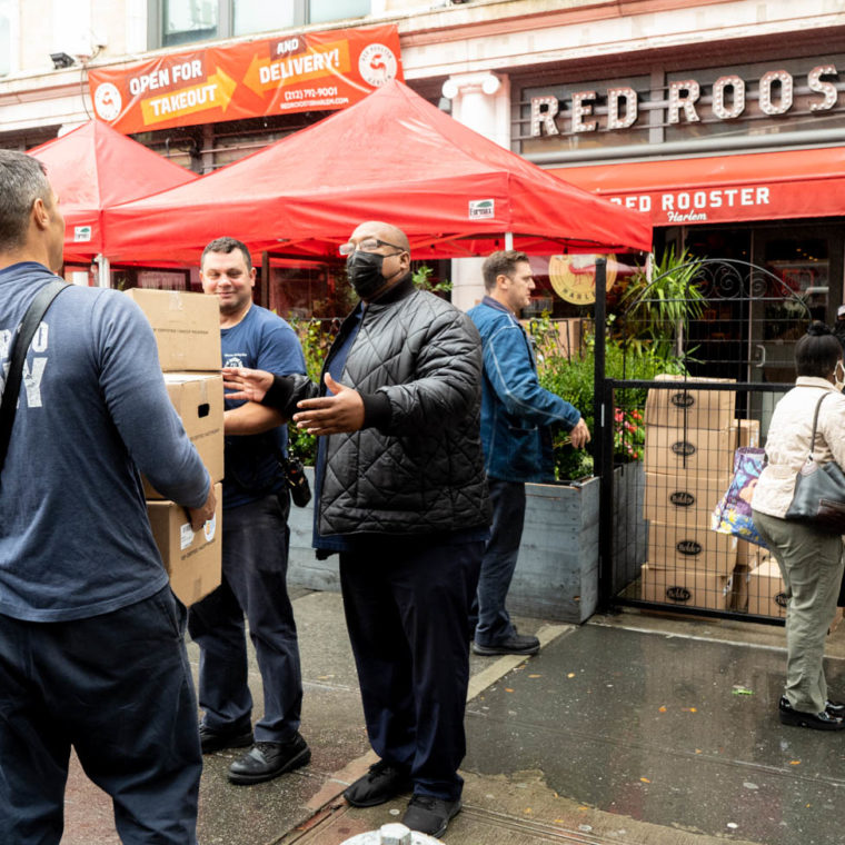"October 13, 2020: Boxes of produce being given to firemen. ""We give to the community,"" explained the masked man in black. Red Rooster Restaurant, 310 Malcolm X Boulevard, Harlem, New York, New York. © Camilo José Vergara"
