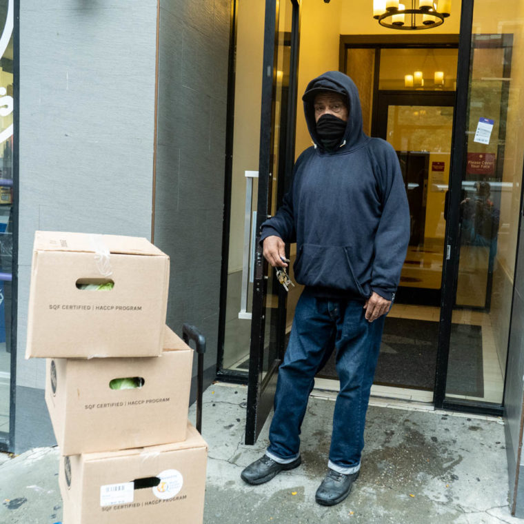 October 13, 2020: Joe, a retired sanitation worker, carrying boxes of free produce from Red Rooster Restaurant. He brought the boxes for elderly and sick residents of his building who were unable to get it themselves. 17 West 125th Street, Harlem, New York, New York. © Camilo José Vergara