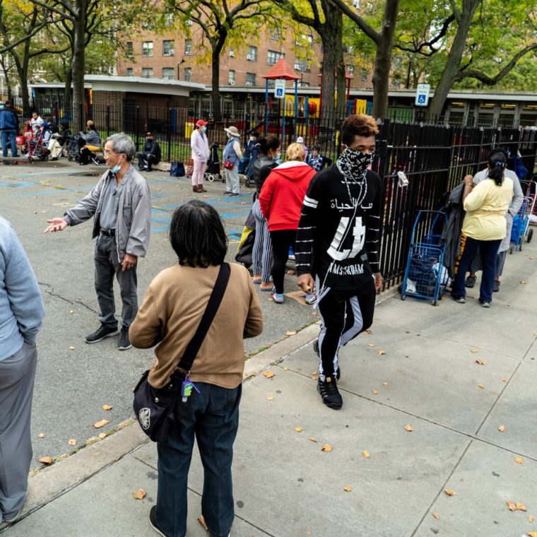 October 21, 2020: Waiting for the 4:00 pm food truck. Public housing parking lot, Powell Street at Sutter Avenue, Brooklyn, New York. © Camilo José Vergara