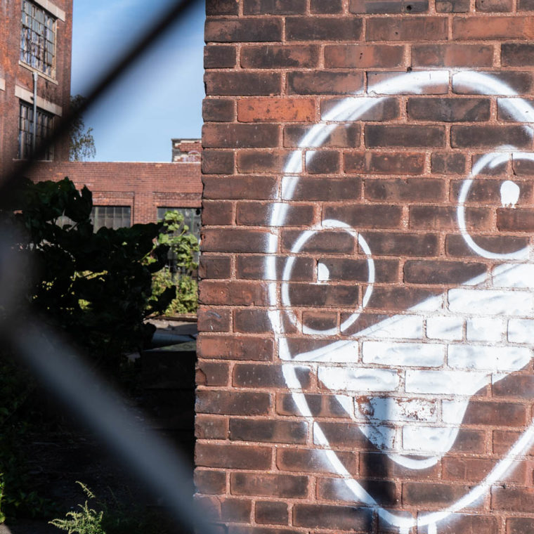 September 22, 2020: Face wearing a mask on a wall of the ruined Remington Plant. Helen Street at Maple Street, Bridgeport, Connecticut. © Camilo José Vergara