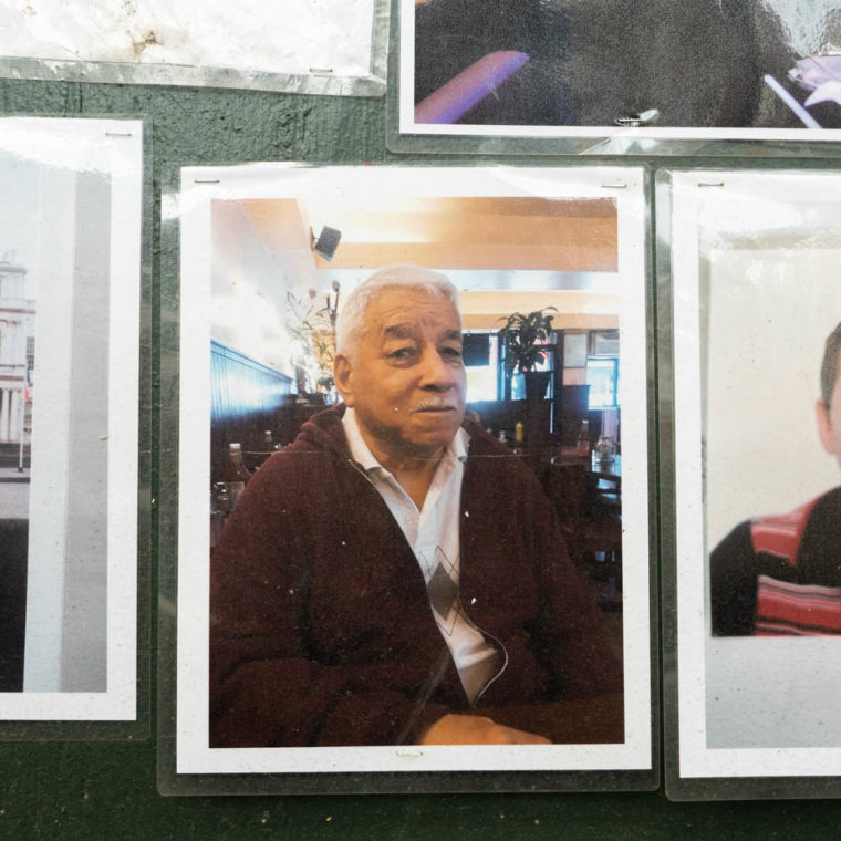 """August 9, 2020: Rodrigo Caleno (left) and Carlos Ortiz (center), victims of the pandemic. """"Memorial to Those Who Walked With Us,"""" by Make the Road New York, depicting young and old residents of Corona killed by Covid-19. 104-21 Roosevelt Avenue, Queens, New York. © Camilo José Vergara"""